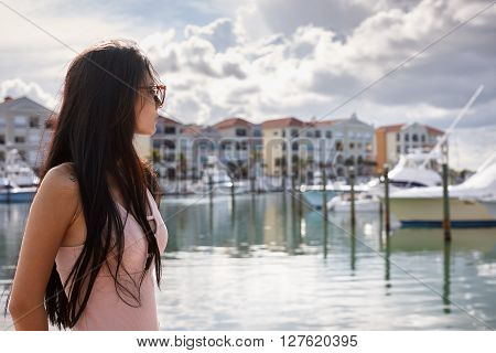 Young woman in sunglasses portrait in a yacht harbour
