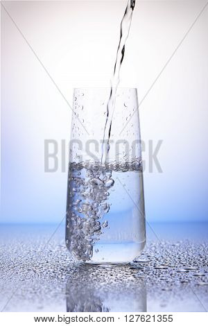 Water Pouring Into Half-filled Drinking Glass In Drops Of Water