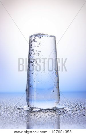Full Drinking Glass With Reflection In Drops Of Water