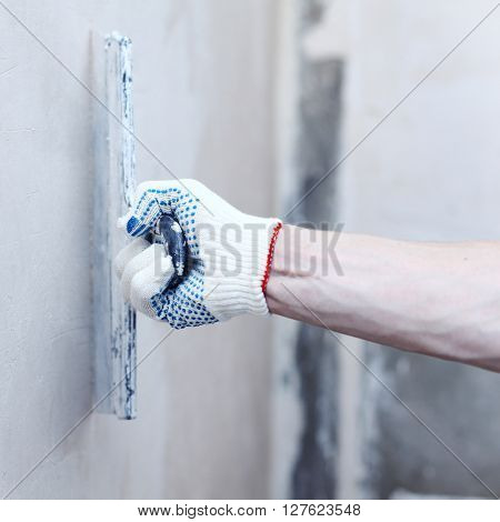 Man aligns the walls with stucco close up