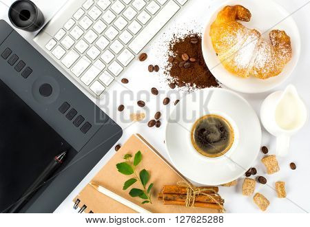 Top view of coffee composition on a white background. espresso cup with croissant, graphics tablet, sketch book.