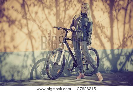 Young blonde girl is standing near bike, toned photo