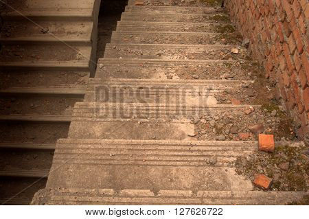 Concrete down stairs with moss concrete pieces and broken bricks.