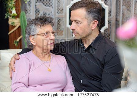 Man comforting elderly lady