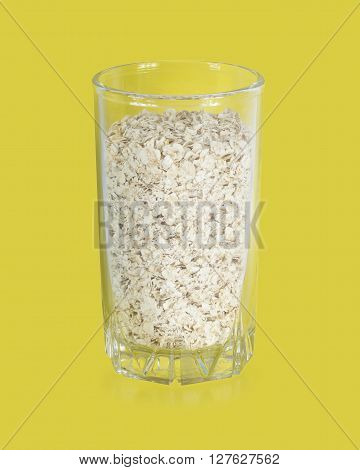 Rolled oats (oat flakes) in a glass on a yellow background.