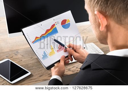 Close-up Of A Businessman Analyzing Graph