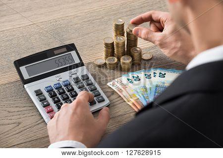 Close-up Of A Businessman Calculating Profit