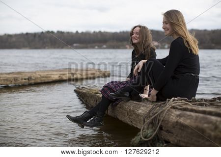 Cute girls sitting on a log and laughing near the river.