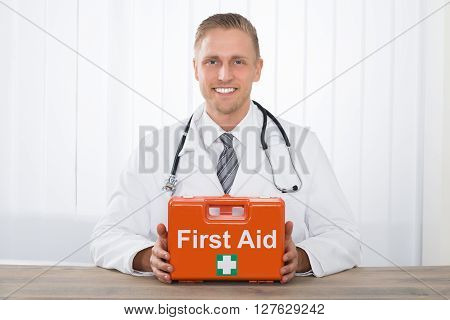 Smiling Male Doctor Holding First Aid Kit