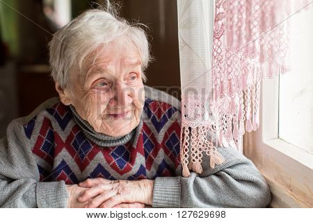 An elderly woman, a grandmother, with a smile looking out the window sitting in the kitchen.