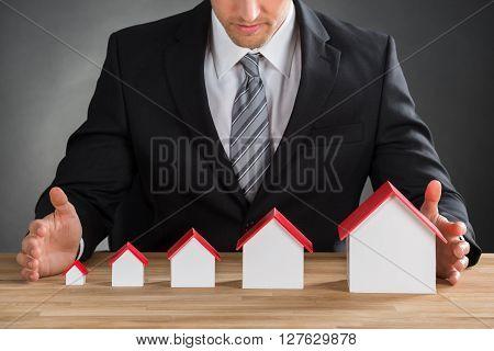 Businessman Shielding House Models