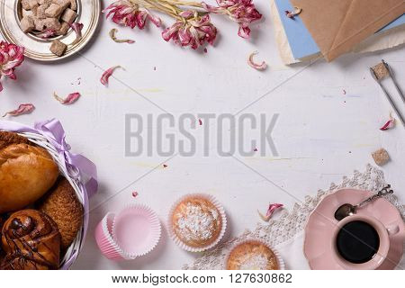 A breakfast served with a variety of pastries, desserts, coffee, sugar and tulip petals. Copy space, top view.