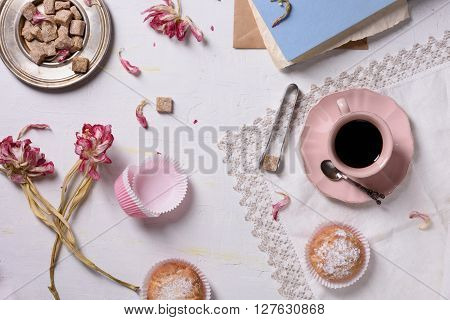 Romantic breakfast, coffee, cupcake desserts and pink flowers served with love. Top view.