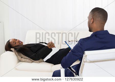 Woman Laying On Couch In Front Of Psychiatrist