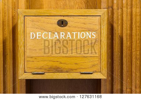 Wall mounted wooden box with declarations painted on it