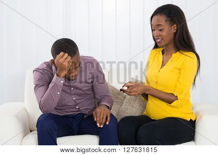 Sad Expectant Couple Sitting On Sofa
