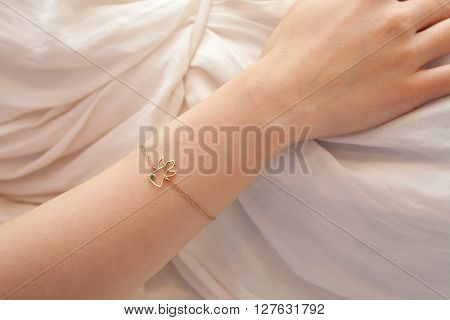 Detail of woman's hand with angel bracelet resting on her belly while relaxing