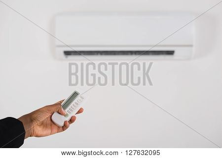 Businesswoman Hand Operating Air Conditioner