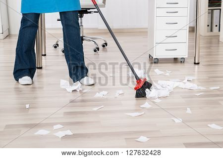 Close-up Of Janitor Sweeping Hardwood Floor