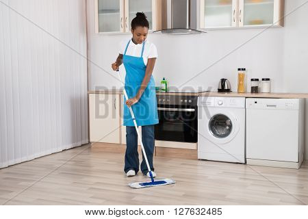 Female Janitor Mopping Floor In Kitchen