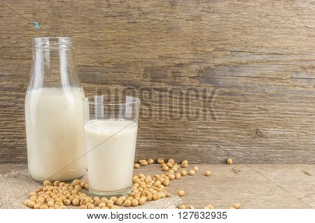 Bottle And Glass Of Soy Milk With Soybeans, On Wooden Background