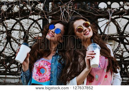 Summer lifestyle portrait of two hipster stylish women with fit sexy body, wearing denim outfit and vintage sunglasses. Girls friends going crazy, having fun, dancing, laughing and screaming