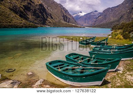 Huaraz, PERU in November 2015: Six green boats are waiting to be sailed across the blue glacier lagoon in the Peruvian Andes. Huaraz is a popular tourist destination for alpine hiking.