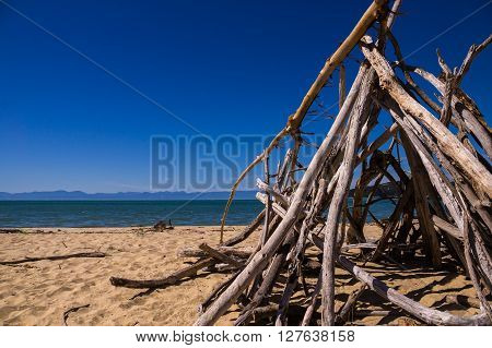 Abel Tasman NP, NEW ZEALAND in February 2016: A tent made out of boughs stands on an empty beach. The sky is blue and the sun is shining.