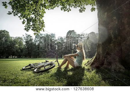 Woman sitting under sun light at day near her bicycle in the park
