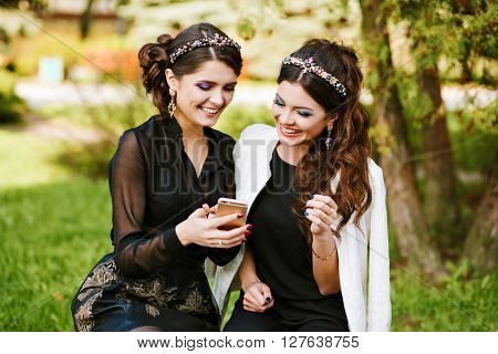 Friend look at the phone and discuss something. Laughing and smiling, going crazy, having fun. stylish woman at the party with a bright evening make-up, fashionable jewelry. Bright colors, warm colors