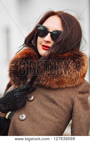 Beautiful Woman in Luxury Fur Coat. Stylish brunette woman in brown coat. young sexy sensual seductive woman with perfect fluffy curled hairs, amazing smile with brilliant white teet, vintage sunglasses