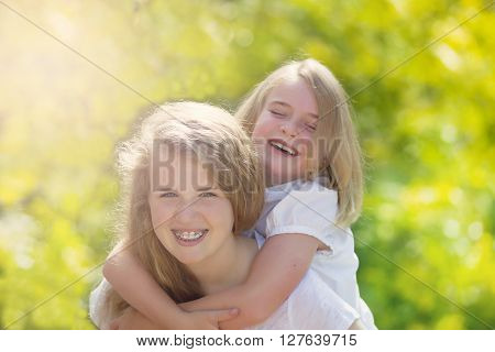 Front forward view with focus on face of older girl of sisters sharing a close moment while outdoors. Light haze effect applied to image.
