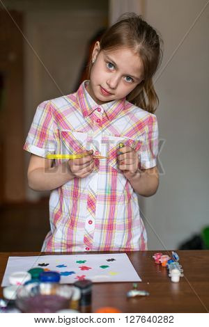 Little girl draws paints.