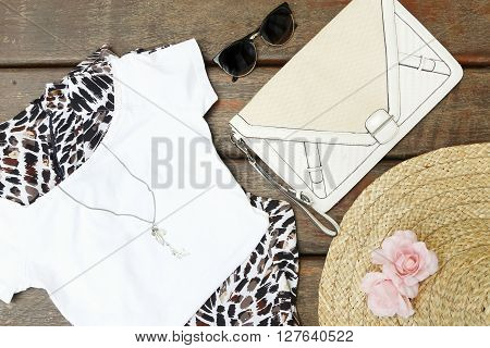 Top view of girly summer outfit on the wooden background