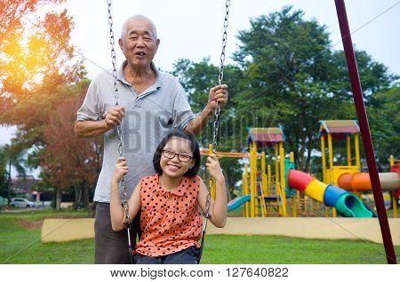 Happy Asian Grandfather posing with his grandchildren