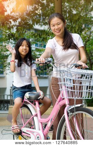 Mother and a daughter cycling bicycle at the park