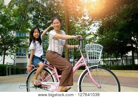 Mother and a daughter cycling bicycle at the park ** Note: Soft Focus at 100%, best at smaller sizes
