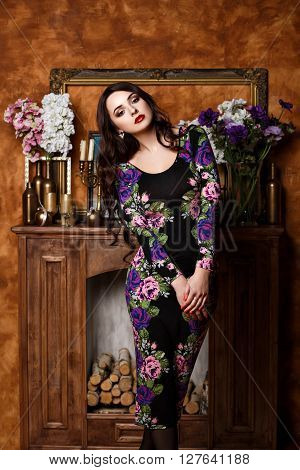 The girl with flowers is standing near the fireplace.  Beautiful girl in evening dress near fireplace. Bright luxury make up. Red lips. Beautiful eyes.