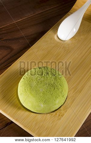 Traditional Japanese mochi with flavor of green tea on a wooden surface