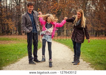 Family of three stand next to each other in park.