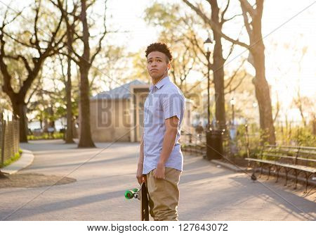 Hispanic skateboarder stands in the park looking far out photographed in New York City in 2016