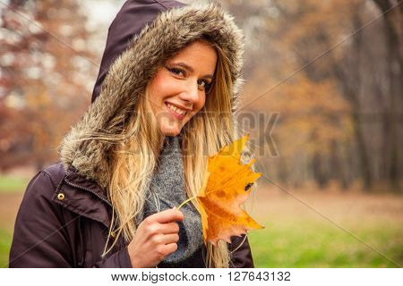 Young woman with hood on head in park holds beautiful leaf.