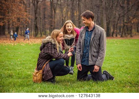 Family of three play around in park.