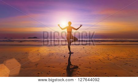 Silhouette of a woman practicing yoga on the ocean beach at amazing sunset.