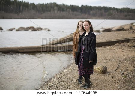 Beautiful girls standing on the shore near the river.