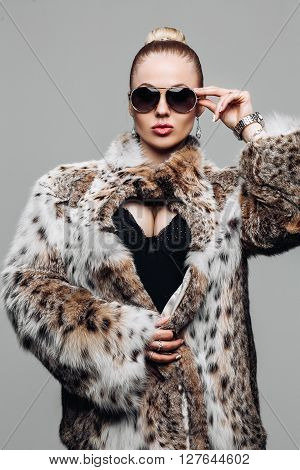 Jewelry and Fashion lady. Beautiful Woman wearing in Luxury Fur Coat over. Portrait of a woman in Studio on a gray background in furs, luxury makeup, luxury bust. Advertise a fur coat from a lynx.
