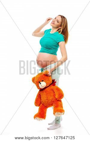 Beautiful pregnant blond woman in pajamas holding a toy bear isolated on a white background. The picture was taken in the Studio