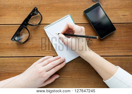education, business and people concept - close up of woman or student writing to notepad with pencil and eyeglasses with smartphone on wooden table