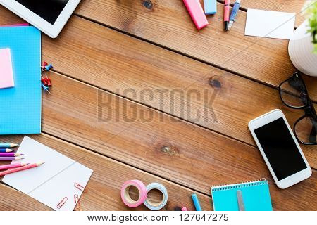 education, school supplies, art, creativity and object concept - close up of stationery and smartphone on wooden table