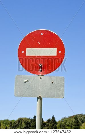 Sunlit red stop sign against blue sky